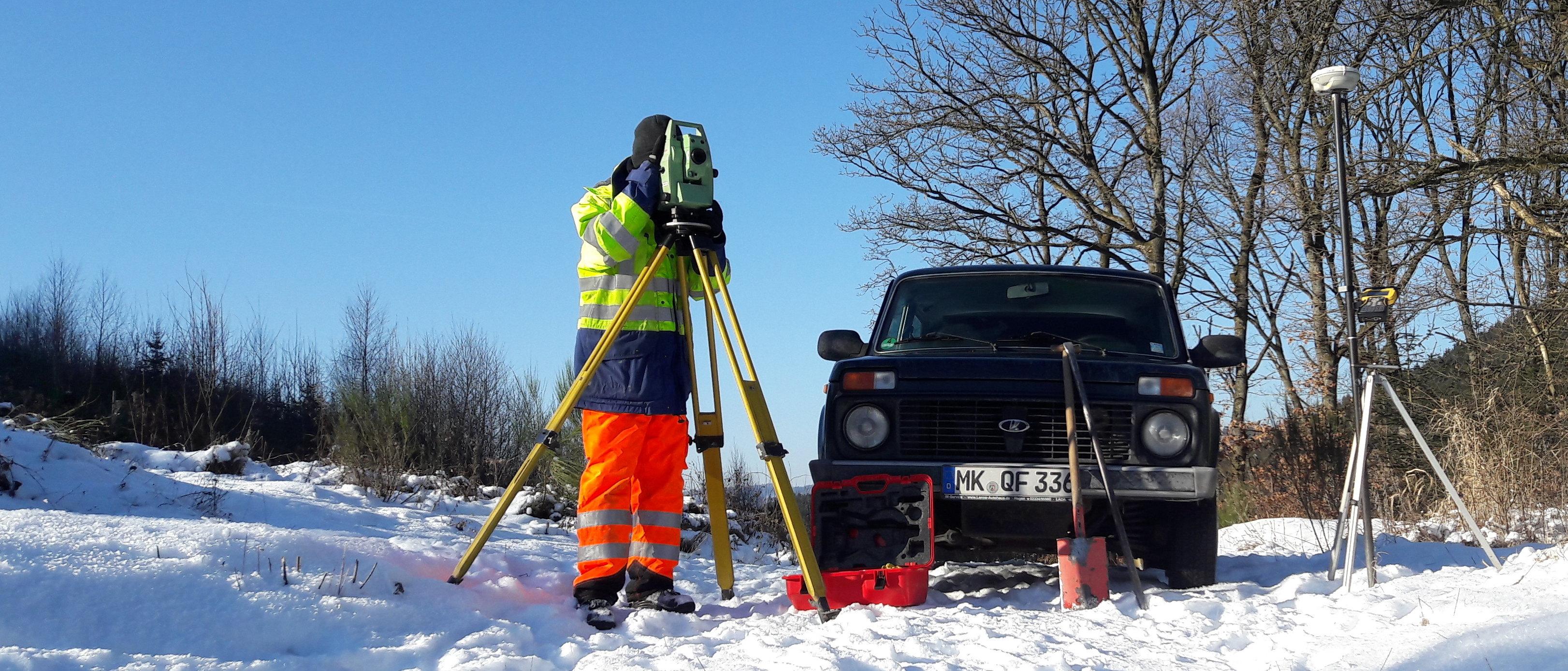 Messgehilfe am Tachymeter im Schnee